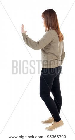 back view of woman. Young woman presses down on something. Isolated over white background. Rear view people collection. backside view of person. . A girl in a gray sweater left hand showing stop sign.
