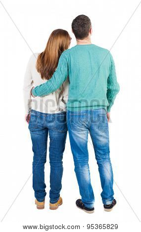 Back view of young embracing couple (man and woman) hug and look into the distance. b  backside view of person.  Isolated over white background. Guy hugs a girl who put her head on his shoulder.