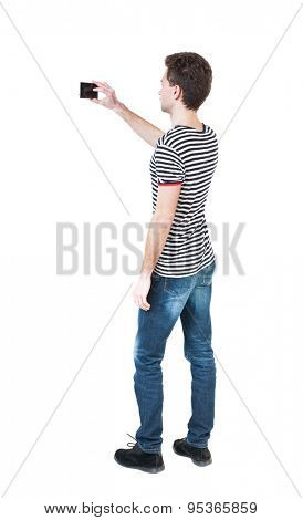 Back view of man with tablet. Standing young guy. Rear view people collection.  backside view of person.  Isolated over white background. The guy in the striped shirt photographs...