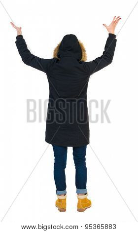 Back view of Beautiful woman in parka looking at wall and Holds  hand up.  young blonde girl standing. The tall girl in a black warm jacket with a hood placed over the head bottomed raised to the sky.