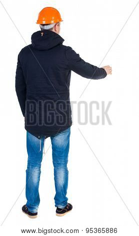 Back view of an engineer in  construction helmet stands.  Standing young guy in parka. Rear view people collection.    Isolated over white background. Engineering teams are working workshop