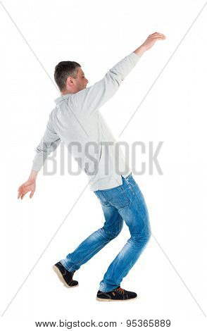Back view man Balances waving his arms. Rear view people collection. backside view of person.  Isolated over white background. A guy in a gray jacket waving his arms in the fall.