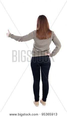 Back view of  woman thumbs up. Rear view people collection.   slender blonde in a jeans shows the symbol of success or hitchhiking. left-handed girl in a gray jacket shows the big finger.