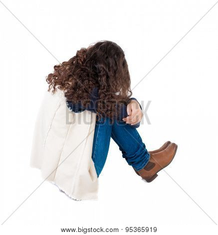 back view curly girl sitting and crying. girl relaxes. Rear view people collection. backside view of person. Isolated over white background.  Girl in sleeveless sheep sitting on the floor and crying.