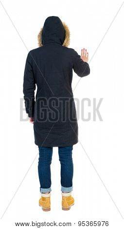 Back view of  pointing young women in parka. Young girl gesture. Rear view people collection.   Isolated over white background. The tall girl in a black jacket with warm presses palm of the hand