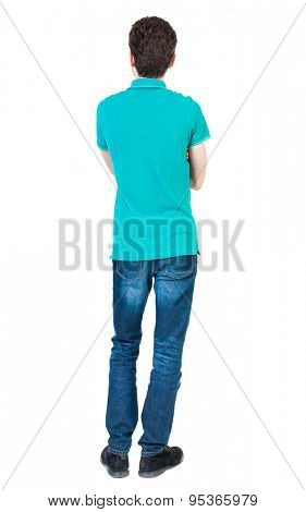 Back view of man in jeans. Standing young guy. Rear view people collection.  backside view of person.  Isolated over white background. A guy in a T-shirt is stylish aquamarine arms folded.