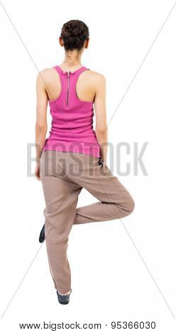Back view of the girl sitting in front warm up exercise.  Rear view people collection.  backside view of person. Isolated over white background. African-American woman standing on one leg doing yoga