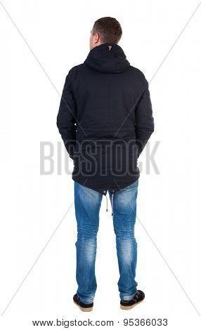Back view of handsome man in winter jacket  looking up.   Standing young guy in parka. Rear view people collection.  backside view of person.  . Man in warm jacket with his hands in his pockets costs.