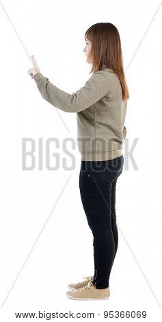 Back view of  pointing woman. beautiful girl. Rear view people collection.  backside view of person.  Isolated over white background. In a sign of the attention the girl lifted her index finger up.