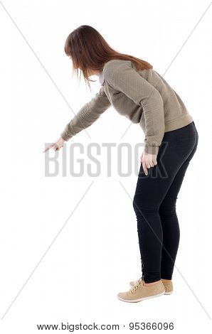 Back view pointing woman. beautiful girl. Rear view people collection.  backside view person.  Isolated over white background.  girl in a gray sweater shows finger of his right hand down somewhere