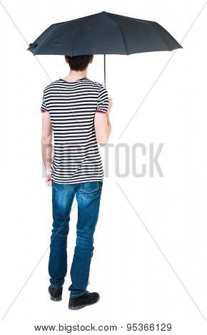 Back view of man in jeans under an umbrella. Standing young guy. Rear view people collection. Isolated over white background. The guy in the striped shirt hiding under an umbrella from the rain.