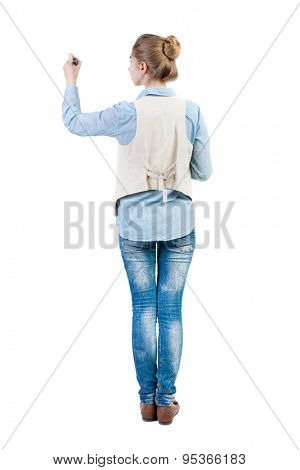 back view of writing beautiful woman. Young girl in jeans draws. Rear view people collection.  backside view of person. Isolated over white background. Girl in sleeveless felt-tip pen draws on wall.