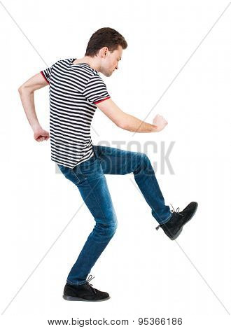 back view of skinny guy funny fights waving his arms and legs. Isolated over white background. Rear view people collection.  Funny guy clumsily boxing. Funny man stands sideways and hit his left fist.