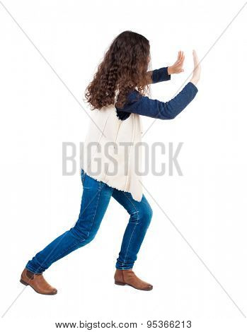 back view of woman pushes wall. Isolated over white background. Rear view people collection. backside view of person.  Girl in sleeveless fleece repels something right.
