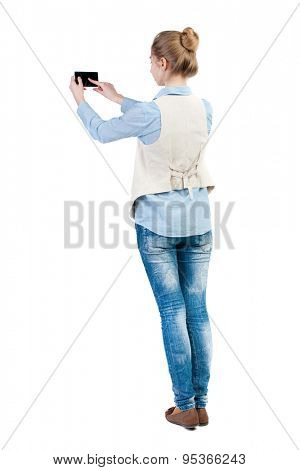 back view of standing young beautiful  woman  in vest and using a mobile phone. girl  watching. Isolated over white background. Girl in sleeveless photographs on the phone in front of something.