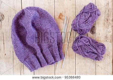 wool purple hat, knitting needles and yarn on wooden background