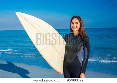 Woman in wetsuit with a surfboard on a sunny day looking at camera
