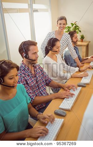 Portrait of female manager assisting staffs in a call center