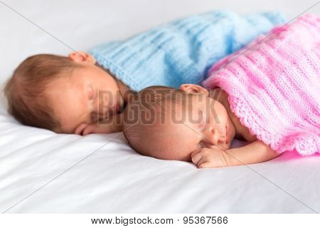 Baby boy and girl twins lying down in bed