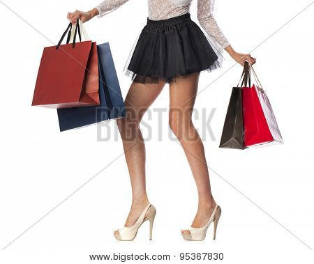 Part body, beautiful female slender legs. Sexy girl holding a paper shopping bags, isolated on white background