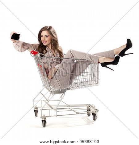 Young beautiful girl photographed themselves on a cell phone while sitting in the shopping cart, isolated on a white background