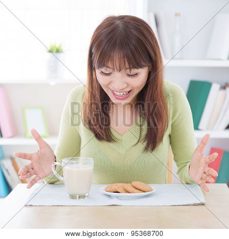 Asian woman feeling surprise with the breakfast, milk and cookies on dining table. Young girl indoors living lifestyle at home.