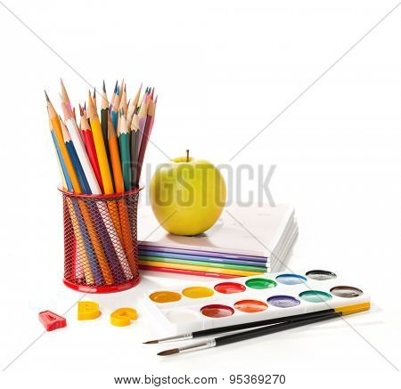 School equipment with pencils, paints ,  brushes and apple  isolated on white. Back to school concept.