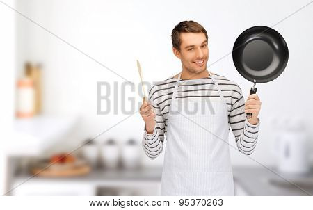 people, cooking and culinary concept - happy man or cook in apron with frying pan and wooden spoon over home kitchen background