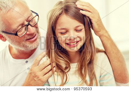 family, support, childhood and people concept - grandfather with crying granddaughter at home