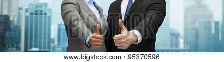 business, people, cooperation, success and gesture concept - businessman and businesswoman showing thumbs up over city background