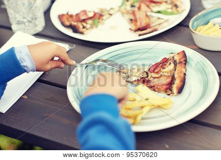 holidays, junk food, dinner, children and people concept - close up of child hands with fork and plate eating pizza at table in summer garden