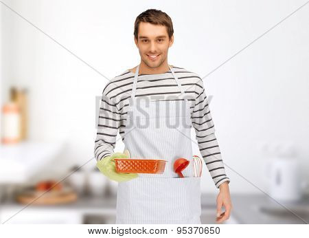 people, cooking, culinary and food concept - happy man or cook in apron with baking and kitchenware over home kitchen background