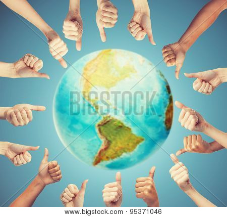 gesture and body parts concept - human hands showing thumbs up in circle over earth globe and blue background