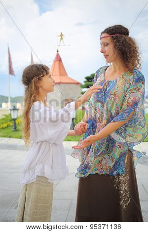Mother and daughter in ethnic dress holding hands near the medieval castle