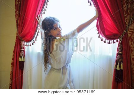 Beautiful girl in ethnic dress opens the red curtains on the window