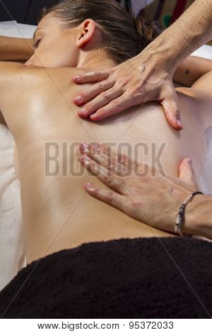 Relaxation. Masseur doing massage on woman body in the spa salon. Beauty treatment concept.