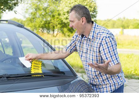 Suprised man looking on parking ticket placed under windshield wiper