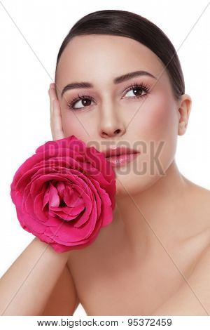 Portrait of young beautiful healthy woman with fancy pink rose looking upwards over white background