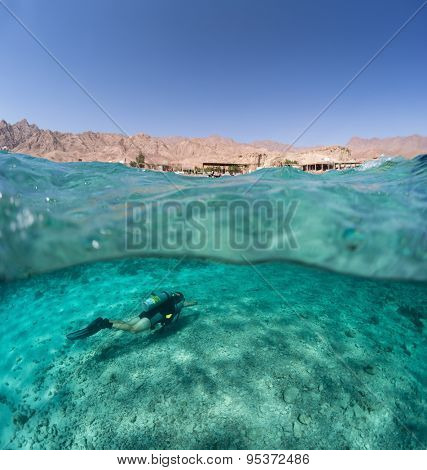 Split shot of the diver underwater and desert coast of the South Sinai above the surface, Egypt
