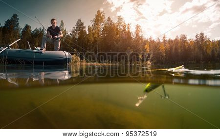Young man fishing on the fresh water pond with surface floating wobbler