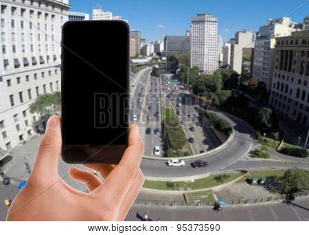 Hand holding mobile smart phone with black screen with Viaduct of Tea in Anhangabau, Sao Paulo on background