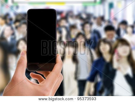 Hand holding mobile smart phone with black screen with a crowd of people in Asia on background