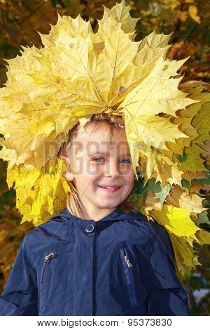 Portrait of cute little girl with maple leaves chaplet enjoying an autumn day outdoors