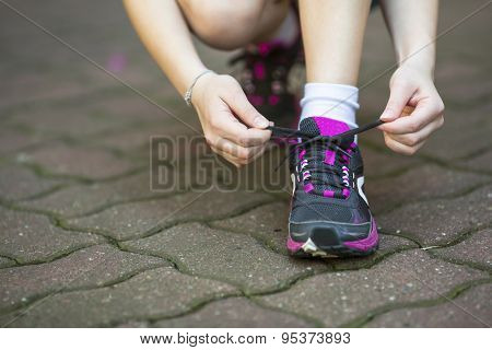 Close-up, girl is tying the laces sports shoe before running.