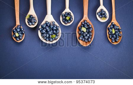 Wild berry. Blueberries in wooden spoons on purple background