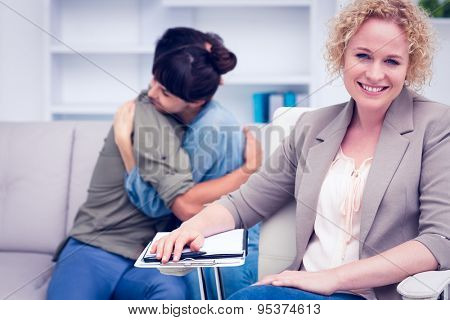 Smiling therapist with comforting patients in the background at therapy session