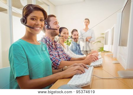 Portrait of pretty call center agent working under a manager supervision