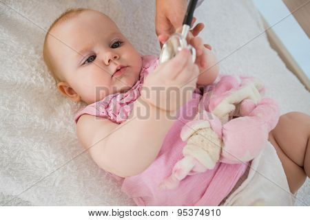 Beautiful cute baby girl with doctor with stethoscope at home in bedroom