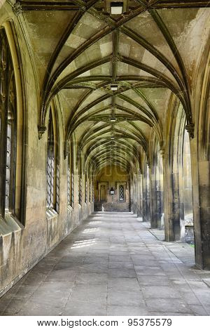 Covered paved stone walkway with Gothic arches receding into the distance and arched windows and portals to the exterior