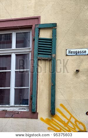 Architectural Detail of Building in Disrepair, Close Up of Window with Broken Shutter and Yellow Graffiti Spray Painted on Wall on Heugasse Street